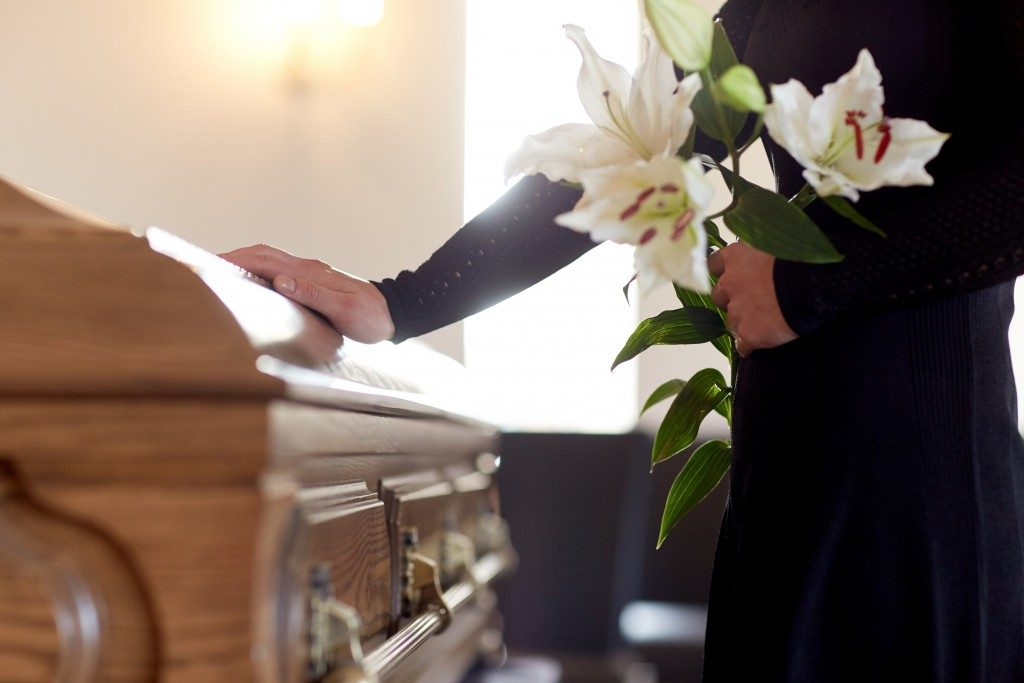mourning woman holding a white flower beside a wooden coffin inside a chapel