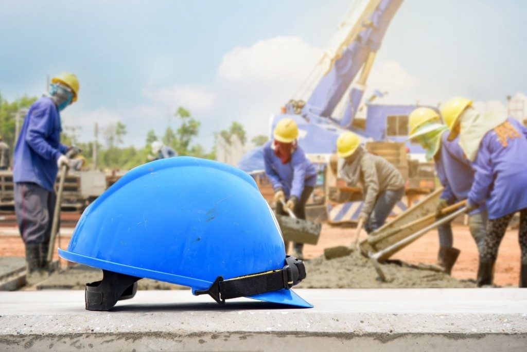 A blue safety helmet with construction workers in the background