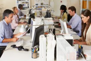 Working At Desks In Busy Office