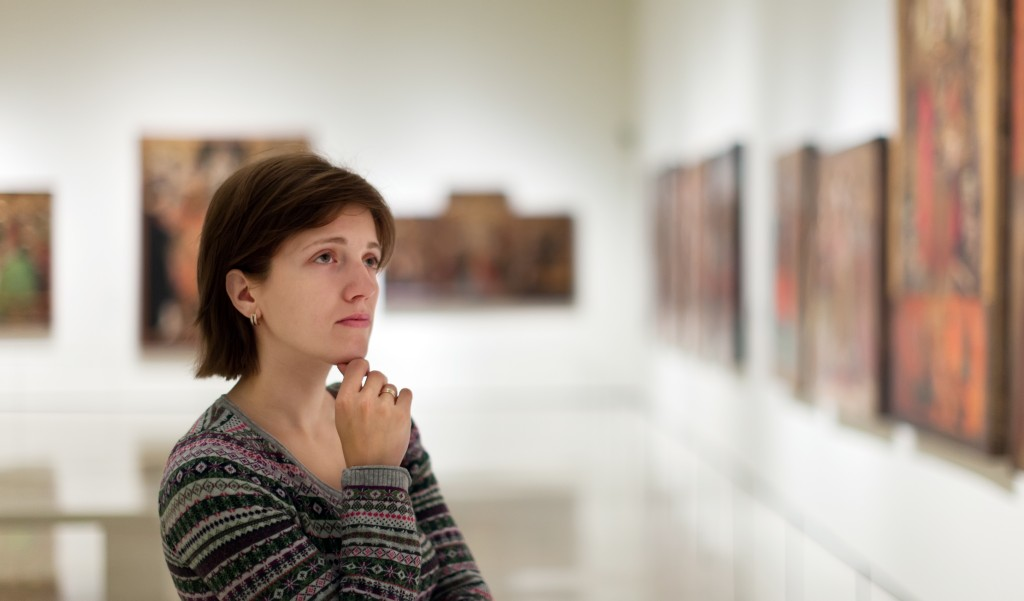 woman looking at the paintings in the art gallery