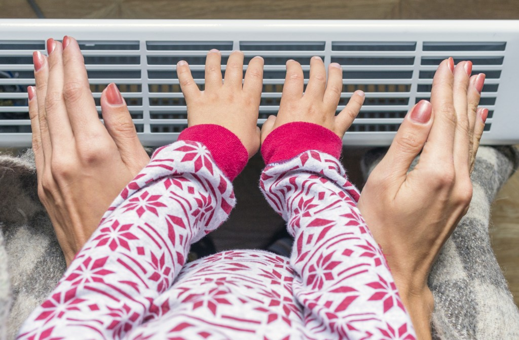Woman and child's hands warm up in a heater