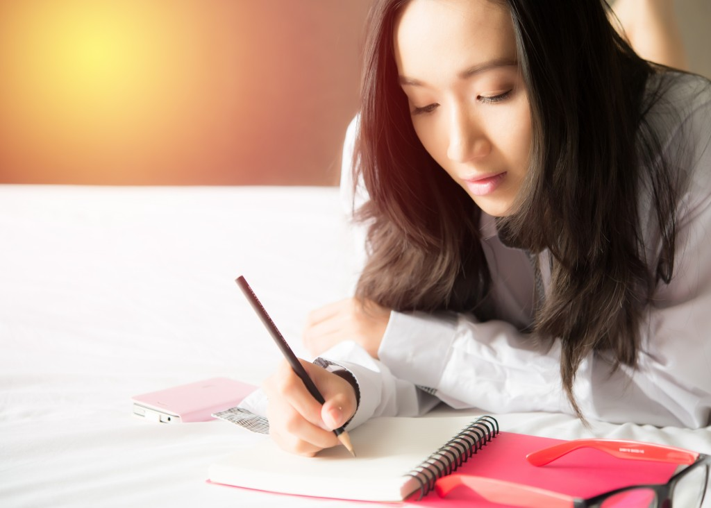 college student writing on her bed