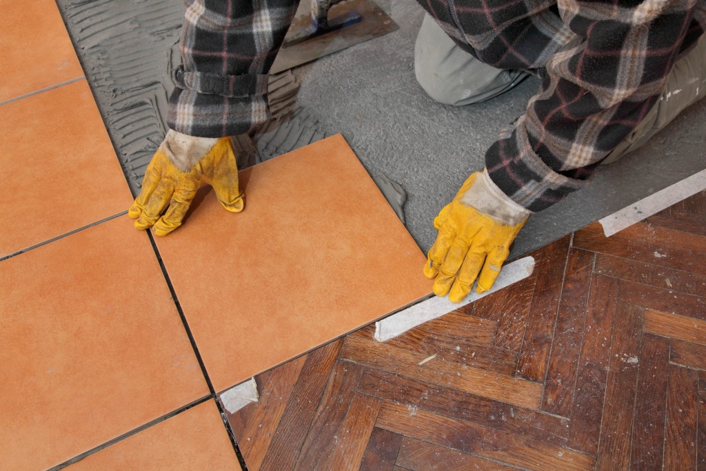man installing new flooring tiles