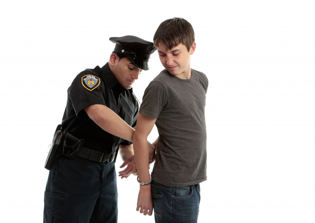 A police officer arrests and handcuffs a young male teen felon