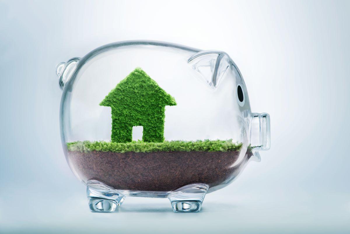 glass piggy bank with a tiny grass house inside