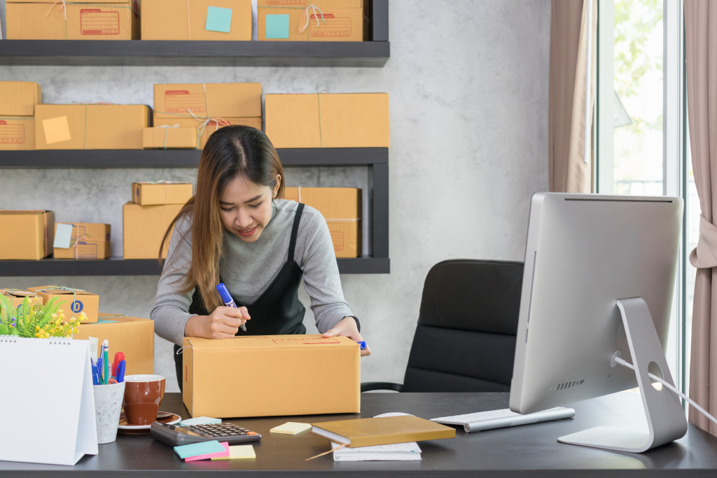 woman writing on a package