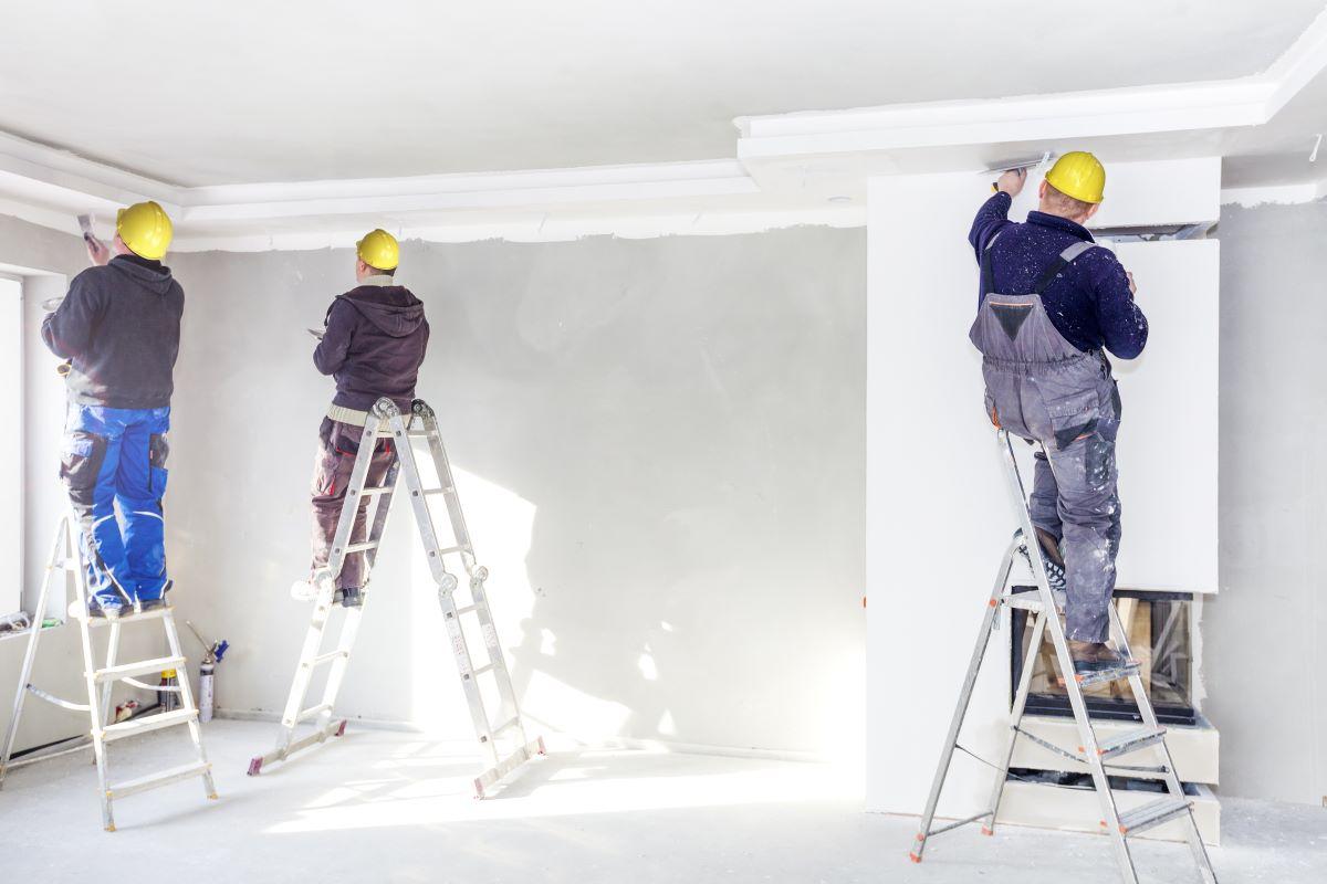 three men painting room