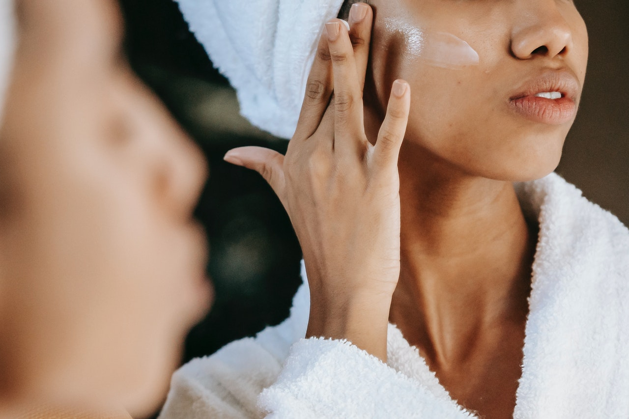 woman applying products to her face