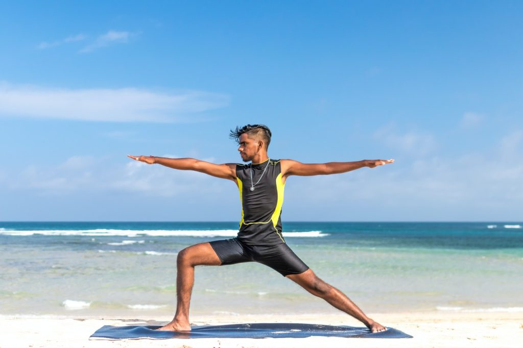 man doing yoga at the beach