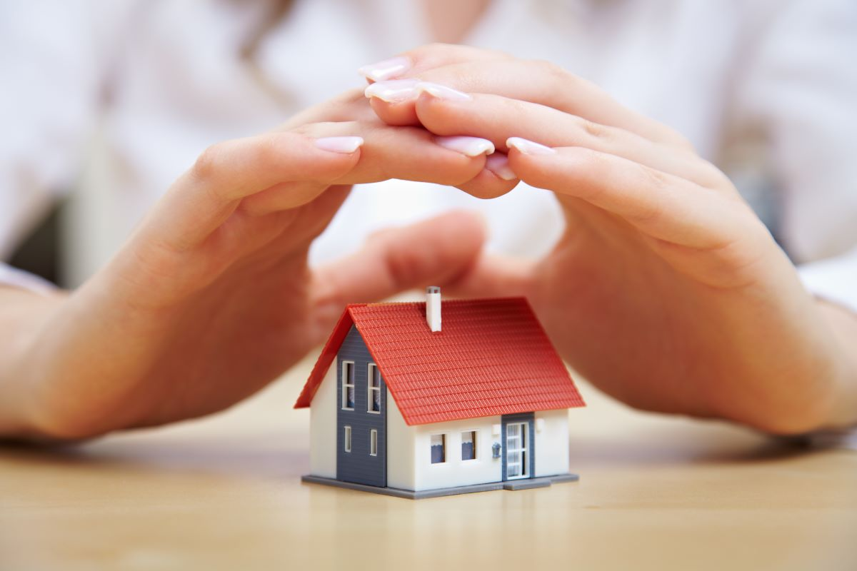 hand hovering over miniature house