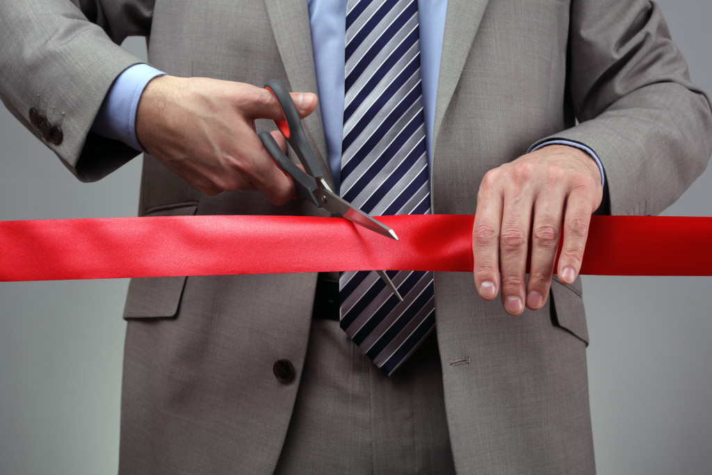man cutting ribbon