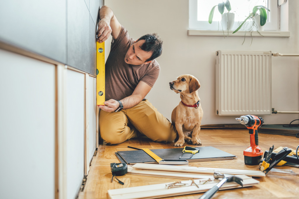man fixing house with dog