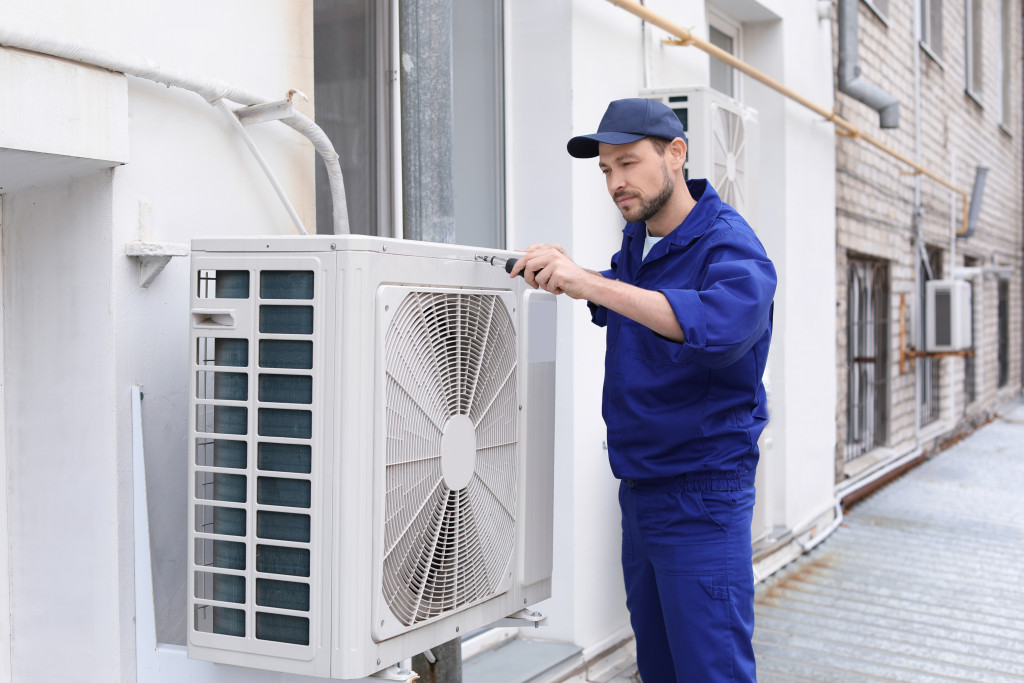 a person checking an air-conditioner